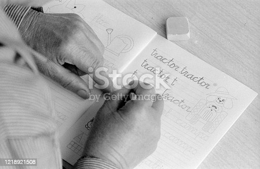 An older lady learns to write Spanish. During adult literacy classes, photo taken in 1983.