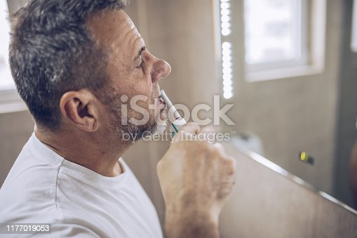 istock An older man brushes his teeth 1177019053