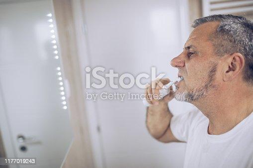 istock An older man brushes his teeth 1177019243