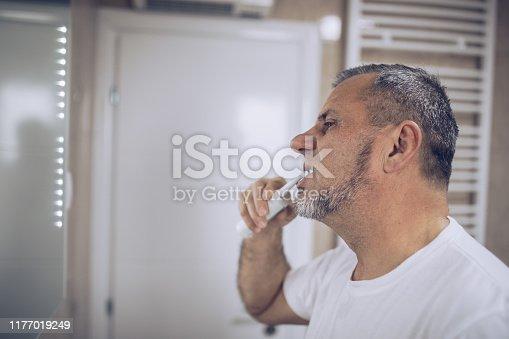 istock An older man brushes his teeth 1177019249