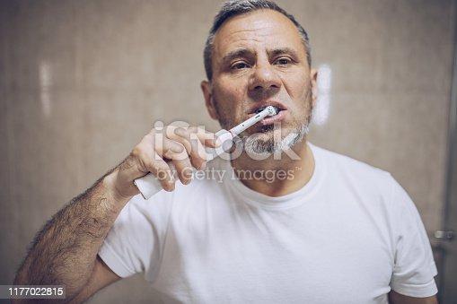 istock An older man brushes his teeth 1177022815
