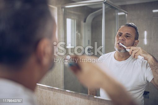 istock An older man brushes his teeth 1179540757