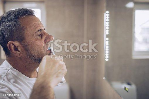 istock An older man brushes his teeth 1179541299