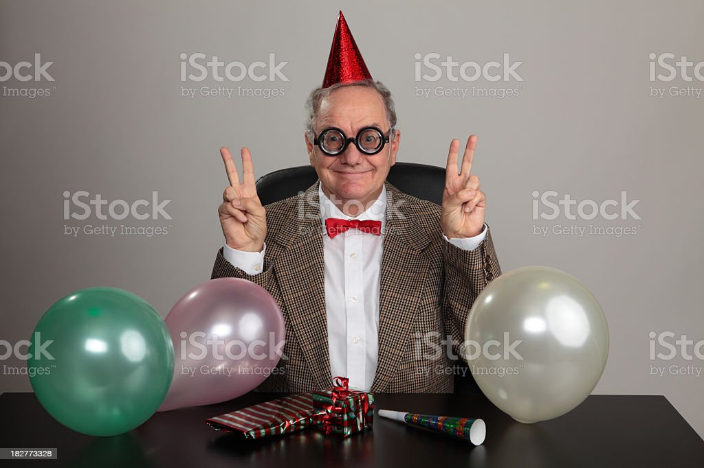 An older man in a party hat with balloons and gifts royalty-free stock photo
