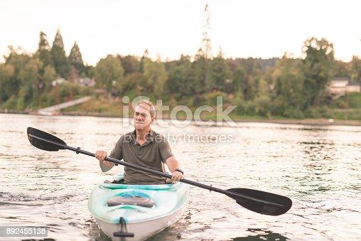 690538774 istock photo An older man kayaks the river on a beautiful summer evening 892455138