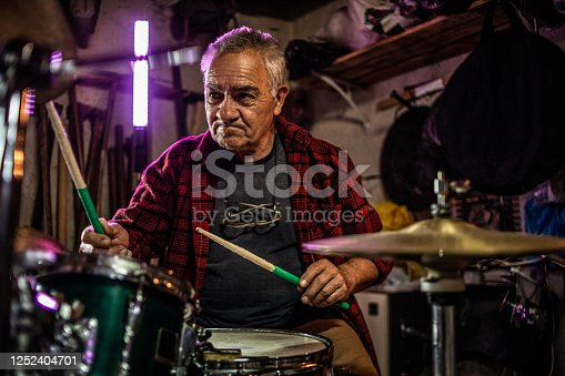 Older man practicing playing bunje - Remembering younger days - Happy older man - Back on stage