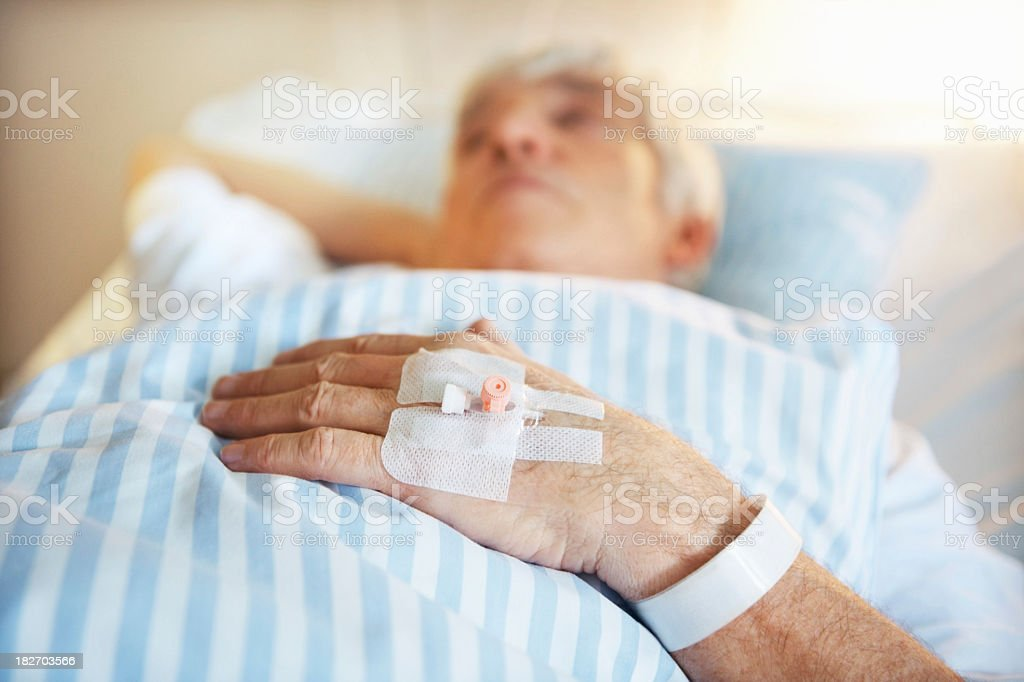 An older patient lying on a bed with an iv in hand royalty-free stock photo