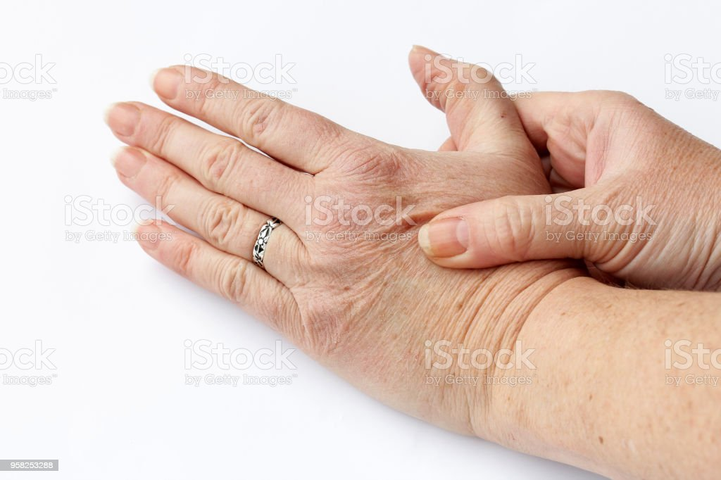 An older woman has pain in her hands stock photo