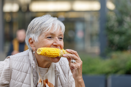 Senior Woman is Walking Through the City Streets and Eating a Baked Corn During an Autumn Afternoon.