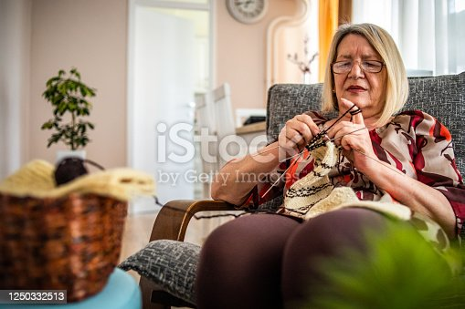 An elderly woman, a pensioner, knits wool socks. An active older woman pursues her hobby