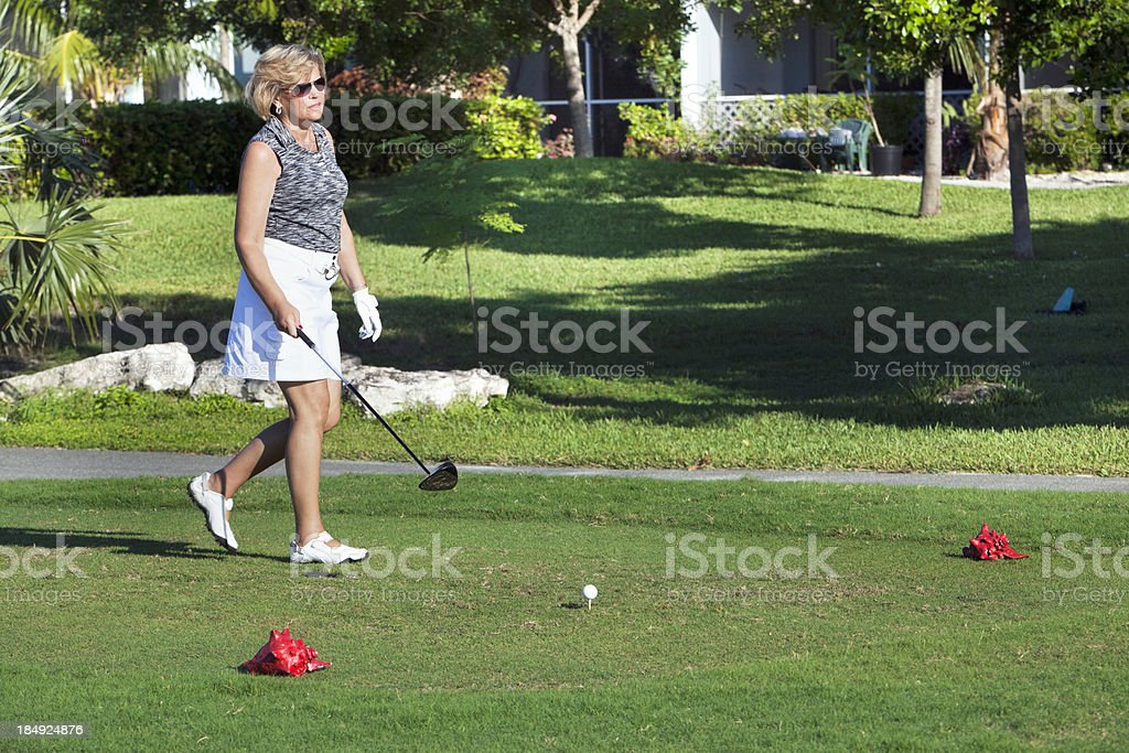 An older woman playing golf in shorts. royalty-free stock photo