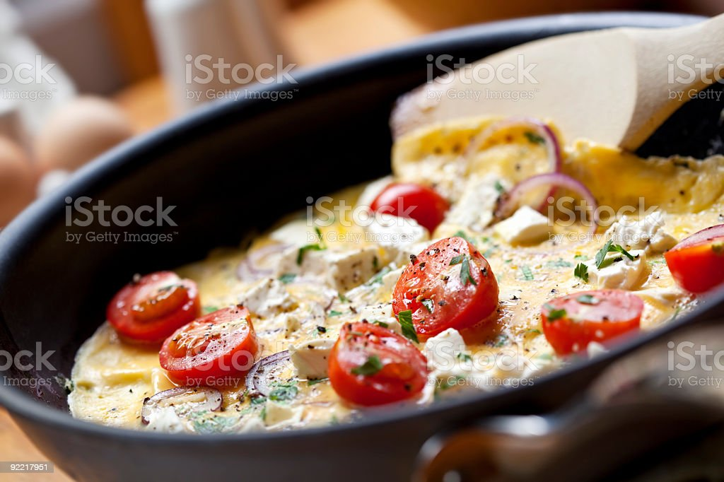 An omelette in a pan with tomatoes on it stock photo