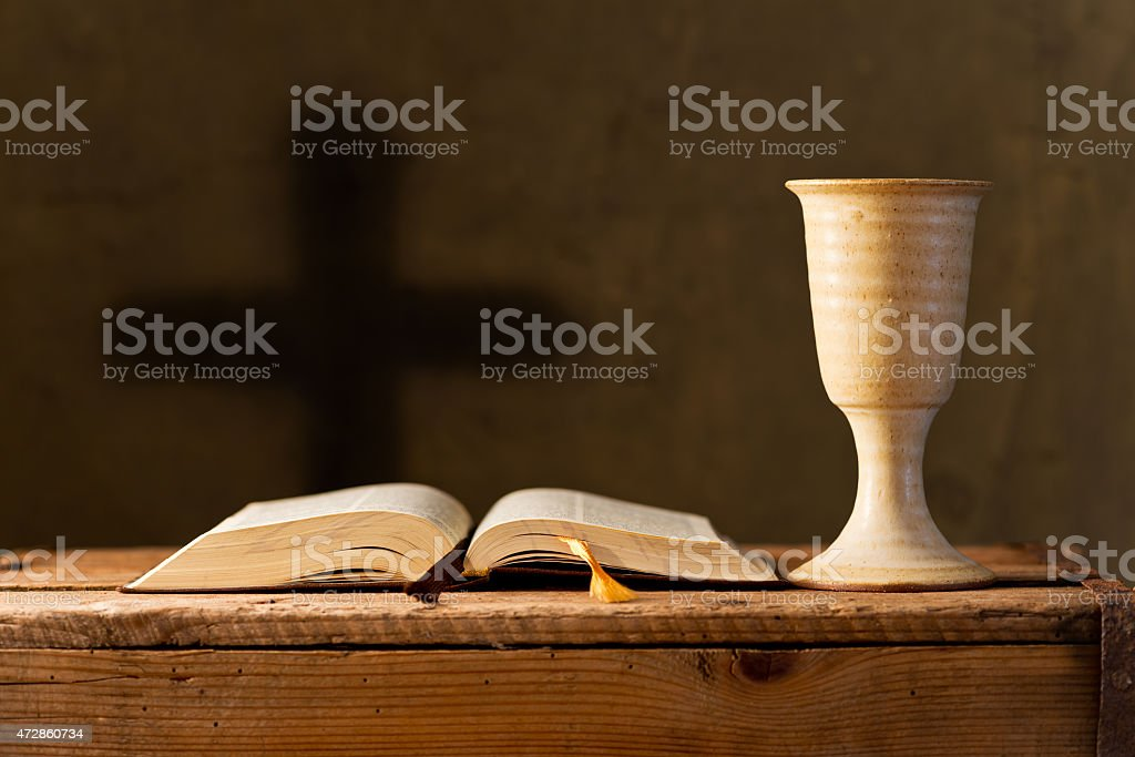 An open bible next to a chalice on a wooden table  stock photo