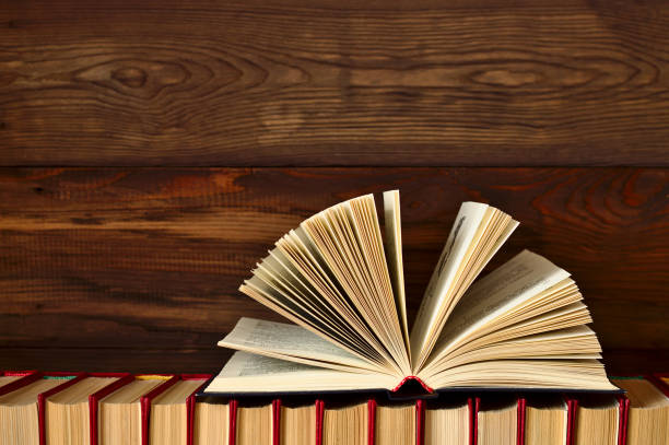An open book lies on a stack of books on a wooden background. stock photo