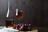 An open bottle of wine next to a glass of pink wine, a bunch of red grapes and a linen table napkin on a wooden board on a wooden background. Place for text.