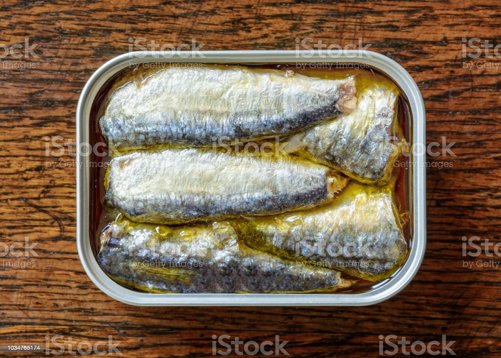 An open can of sardines in oil on a weathered wooden table seen from above. stock photo