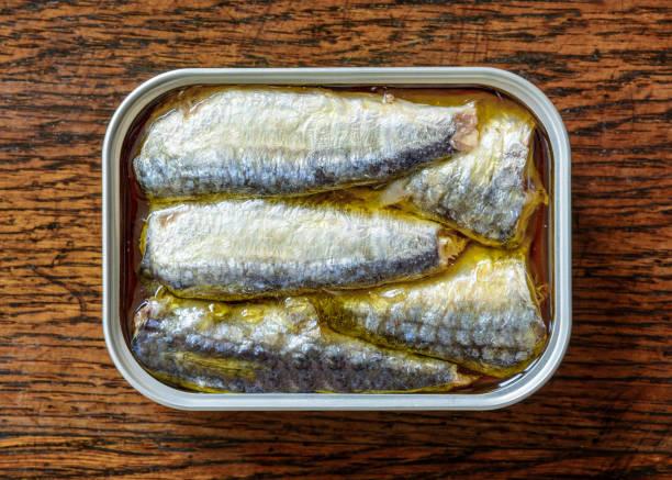 Une belle peut de sardines à l'huile sur une table en bois patinée, vue d'en haut. - Photo