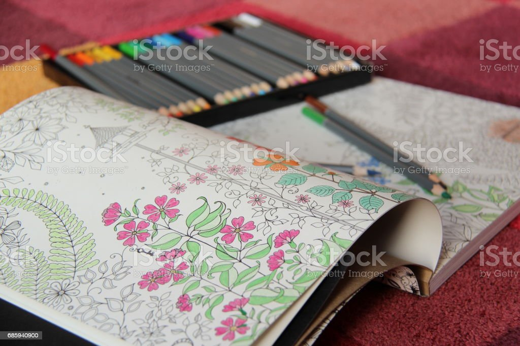 An open coloring book lying on carpet with box of coloring pencils stock photo