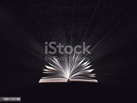 528389419istockphoto An open magic book, bewitched book glows in the darkness, magic light. Education. Dreamy image of a fairytale 1084125188