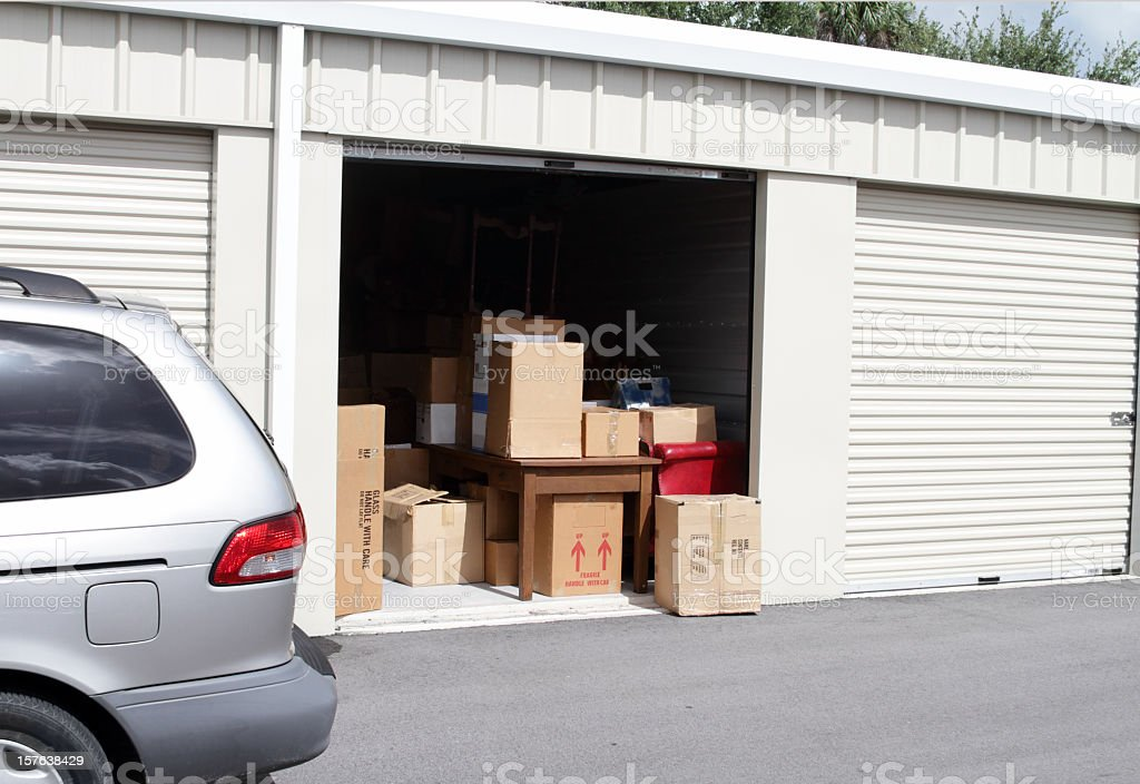 An open self storage unit with a van parked next to it Warehouse building with self storage units. Self storage facility. Roll up doors on self storage facility. One door open with boxes, household goods and furniture in doorway. Van partially visible next to door. Building Exterior Stock Photo