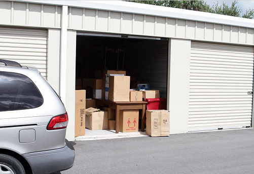 An Open Self Storage Unit With A Van Parked Next To It Stock Photo - Download Image Now
