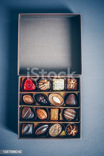 183269671istockphoto An open small box of chocolate pralines and truffles assorted. Blue toned background, directly above. 1057598240