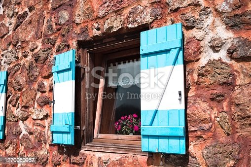 An open window with white and blue wooden shutters of a mountain retreat with stone walls in the Alps (Trentino, Italy, Europe)