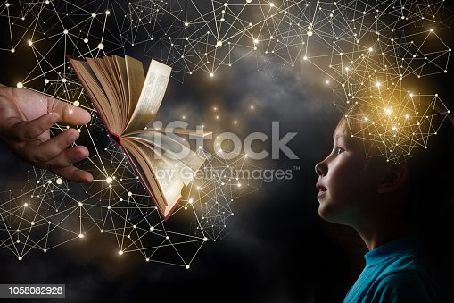 istock An opened book is mooving from an adult's hand towards a child. 1058082928