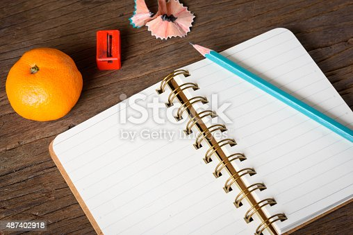 621843818istockphoto An opened notebook with pencil. 487402918