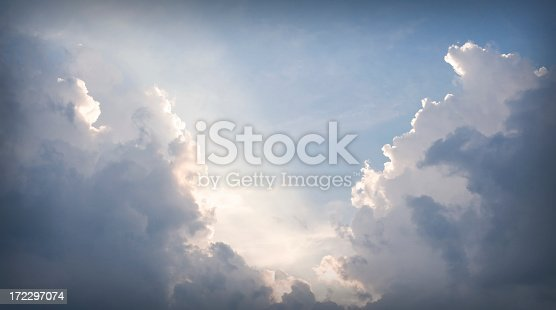 628508634 istock photo An opening in grey clouds revealing sunlight showing the way 172297074