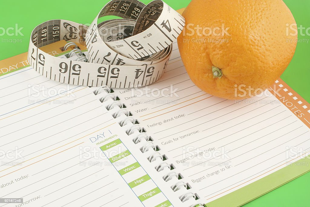 An orange and a tape measure on a blank diet journal royalty-free stock photo