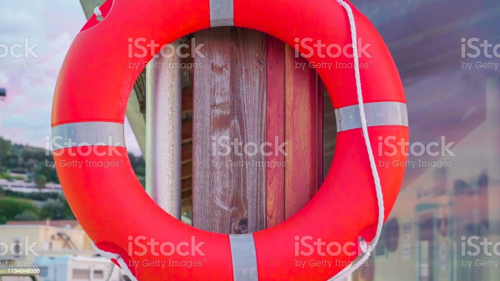An orange and silver color bouy hanging on the wall in Italy stock photo