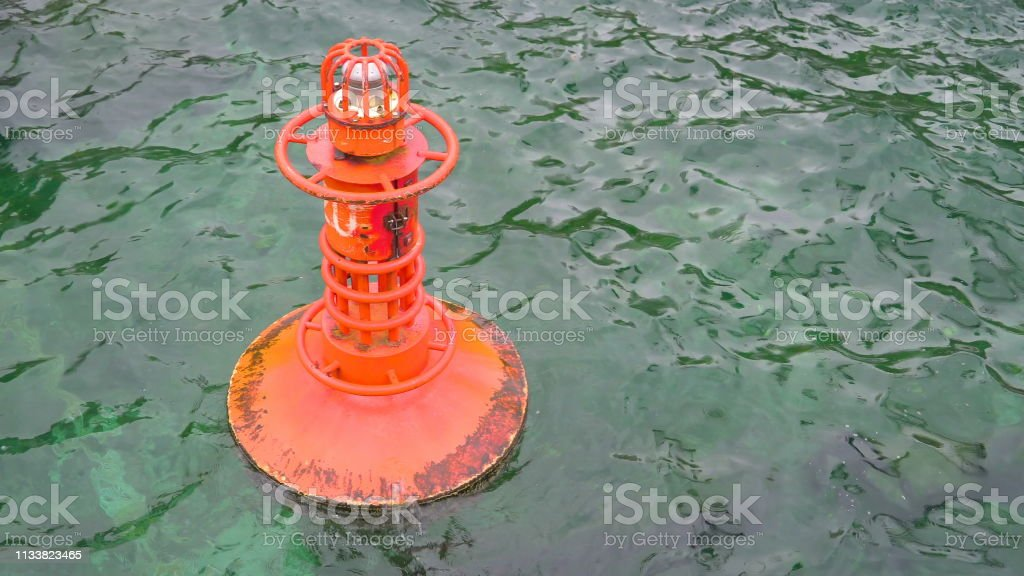 An orange bouy floating in the sea water stock photo