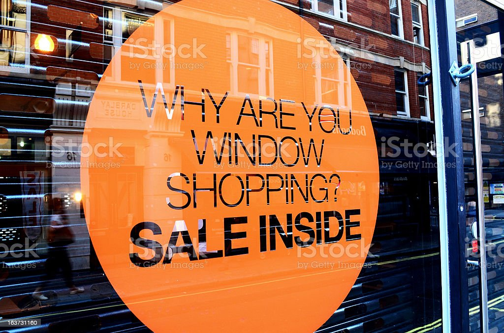 An orange sale sign on a store window stock photo