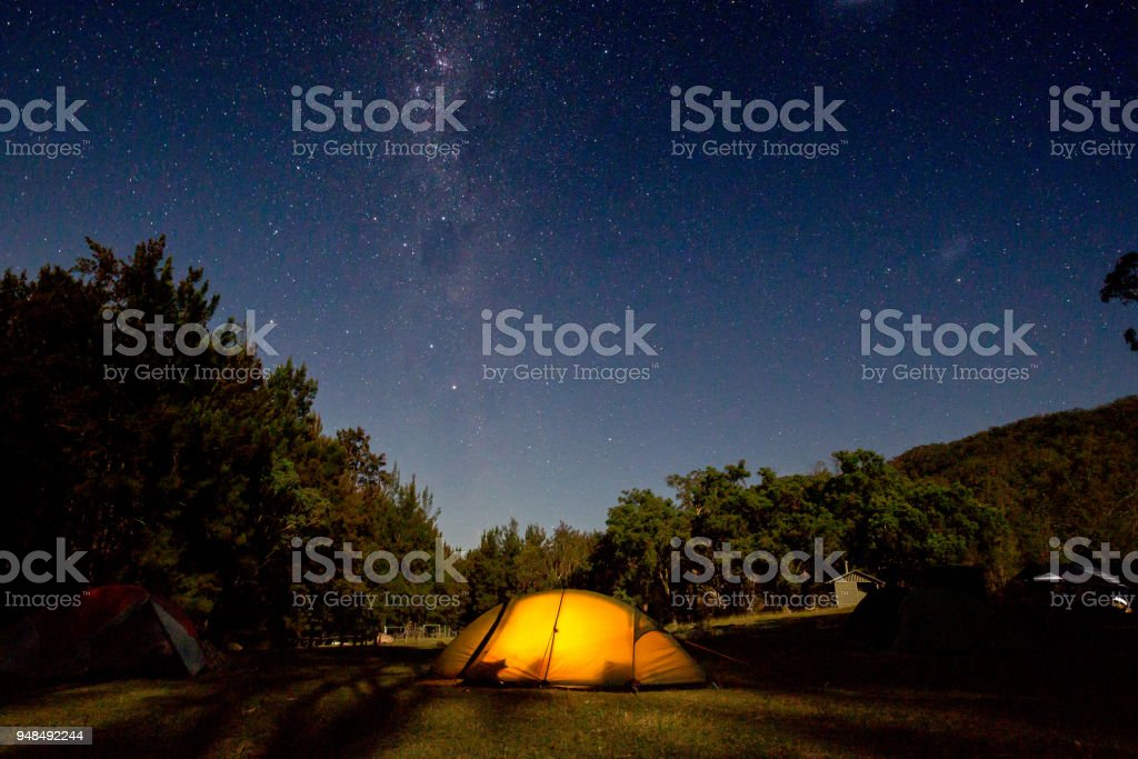 An orange tent glows under a brilliant star filled milky way night sky stock photo