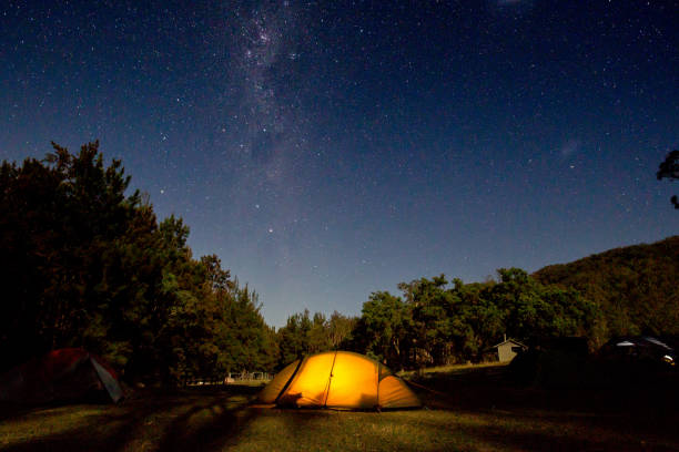An orange tent glows under a brilliant star filled milky way night sky stock photo