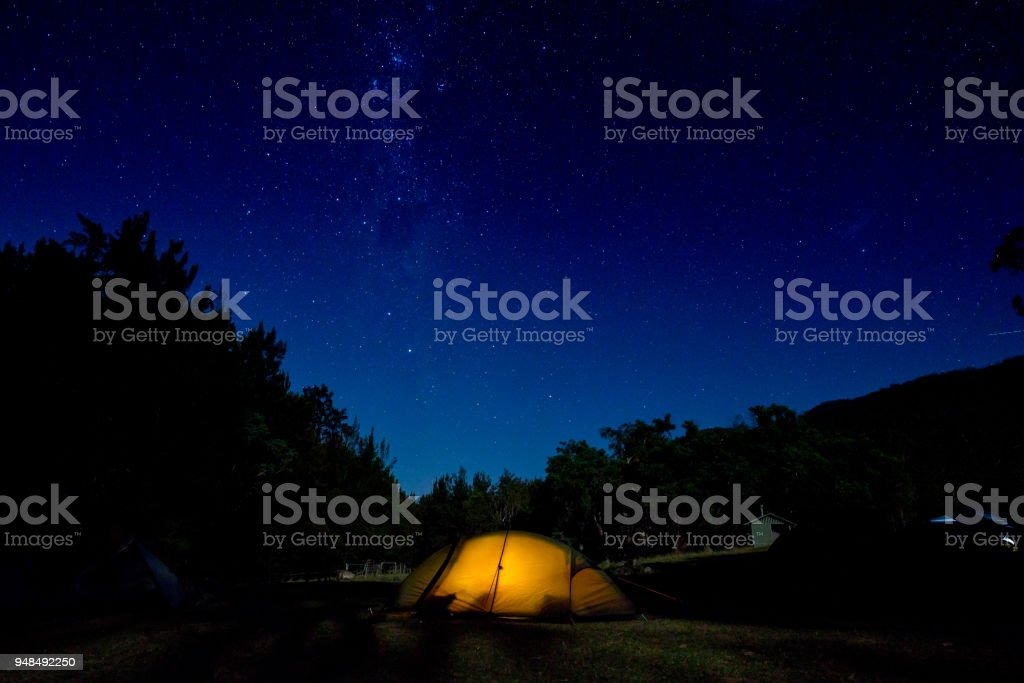 A tent has a light inside it as the stars swirl over a clear night....