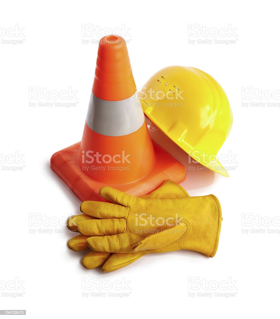An orange traffic cone, builders hat and heavy duty gloves stock photo