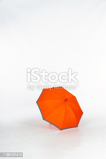 An opened orange umbrella with gray edges in a photo studio on a white background. Isolated on White background, space for text.