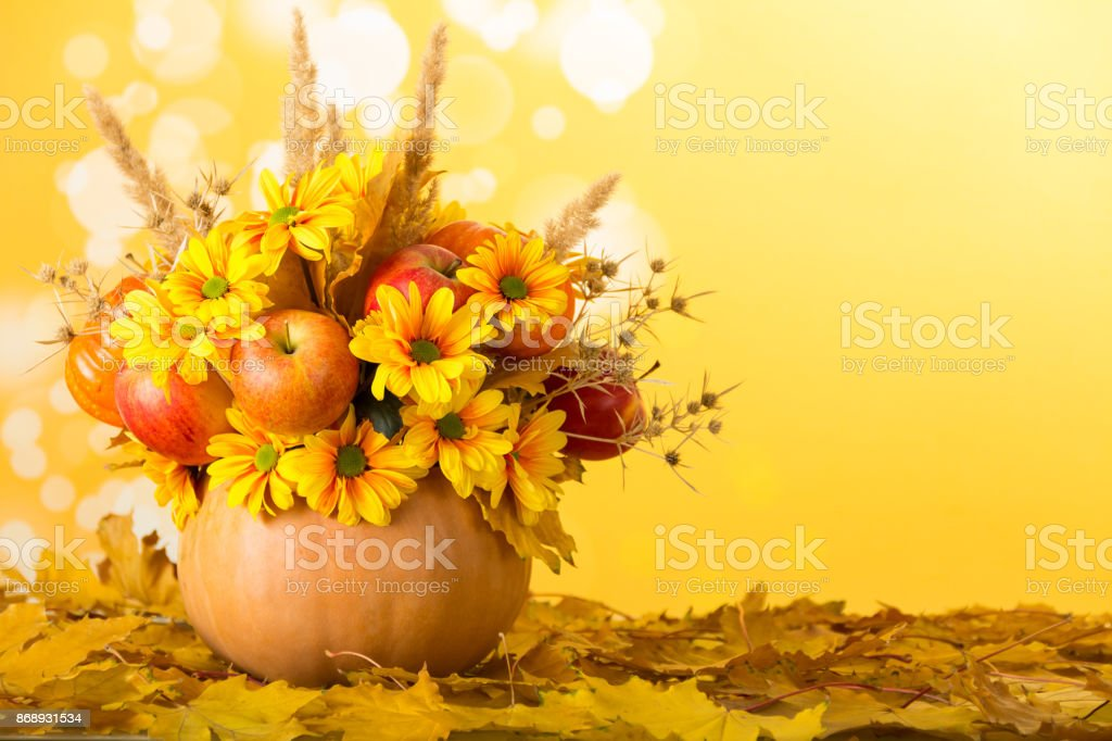 An original bouquet of apples and plants in pumpkin, on autumn leaves stock photo
