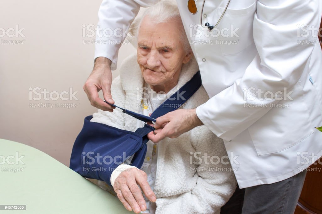 An orthopedic doctor with a stethoscope around his neck puts on an orthopedic collar of a very old woman sitting in a bathrobe on a chair and with her hand in a sling. stock photo