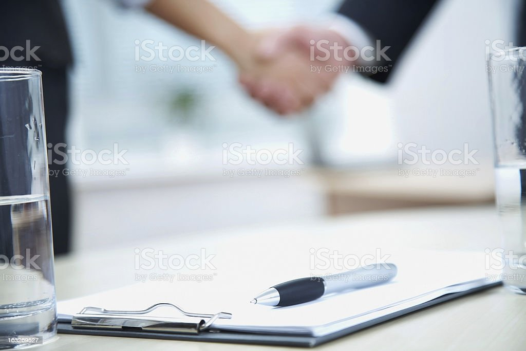 An out of focus business handshake in a office background stock photo