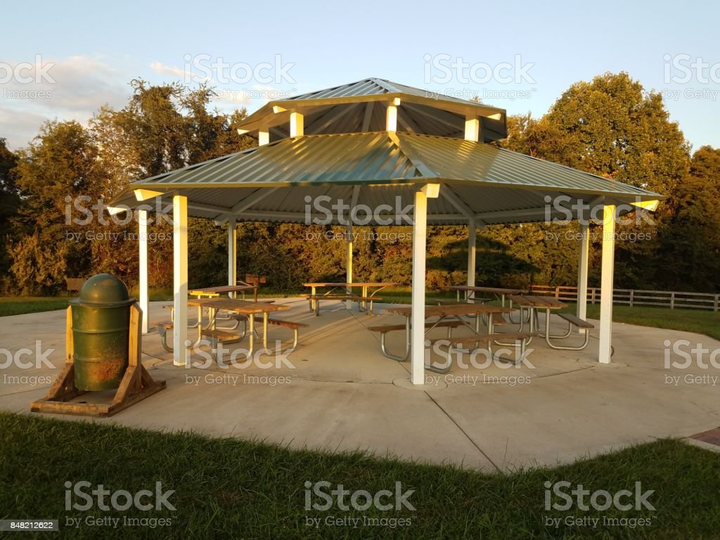 an outdoor pavillion with picnic tables, grill, and trash can stock photo