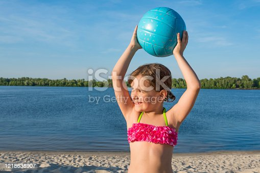 An outdoor portrait of a happy girl with a ball on the beach.  Child having fun on summer vacation.