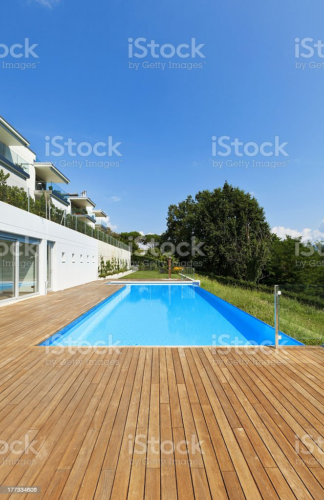 An outdoor swimming pool besides a private house stock photo