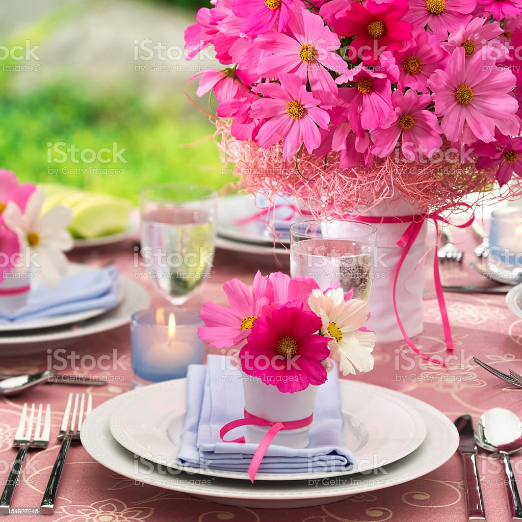 An outdoor tablescape with pink flowers and white China royalty-free stock photo