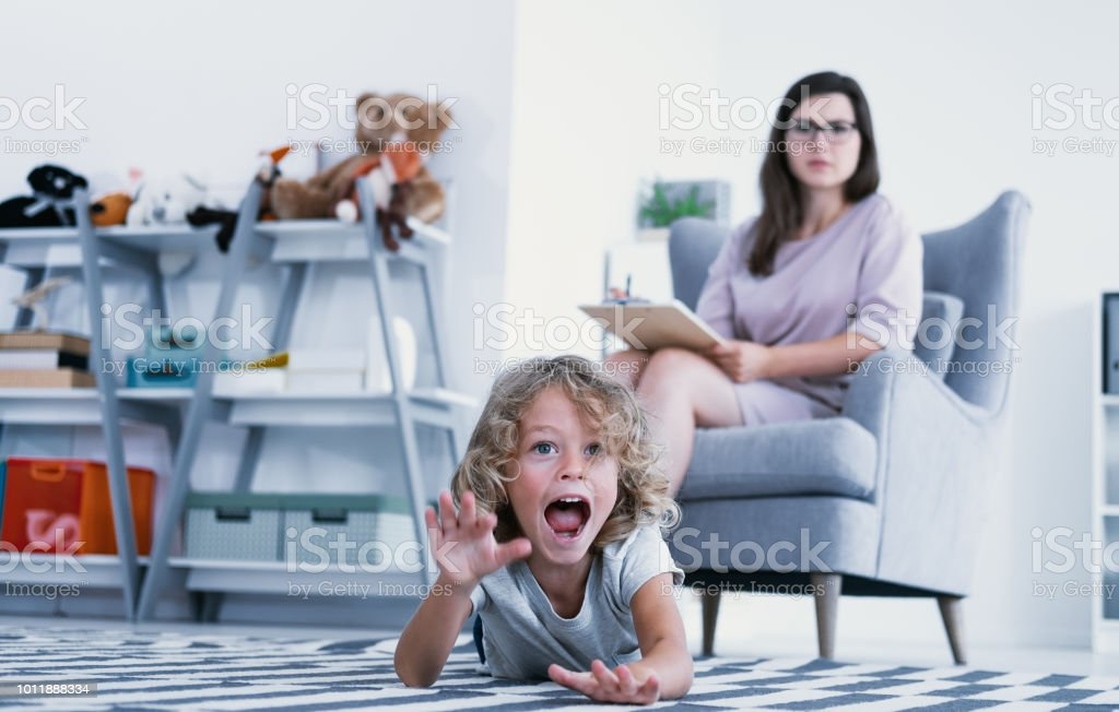 An overactive child screaming and hitting a floor while a psychotherapist is making a diagnose during a meeting in a family support center. stock photo