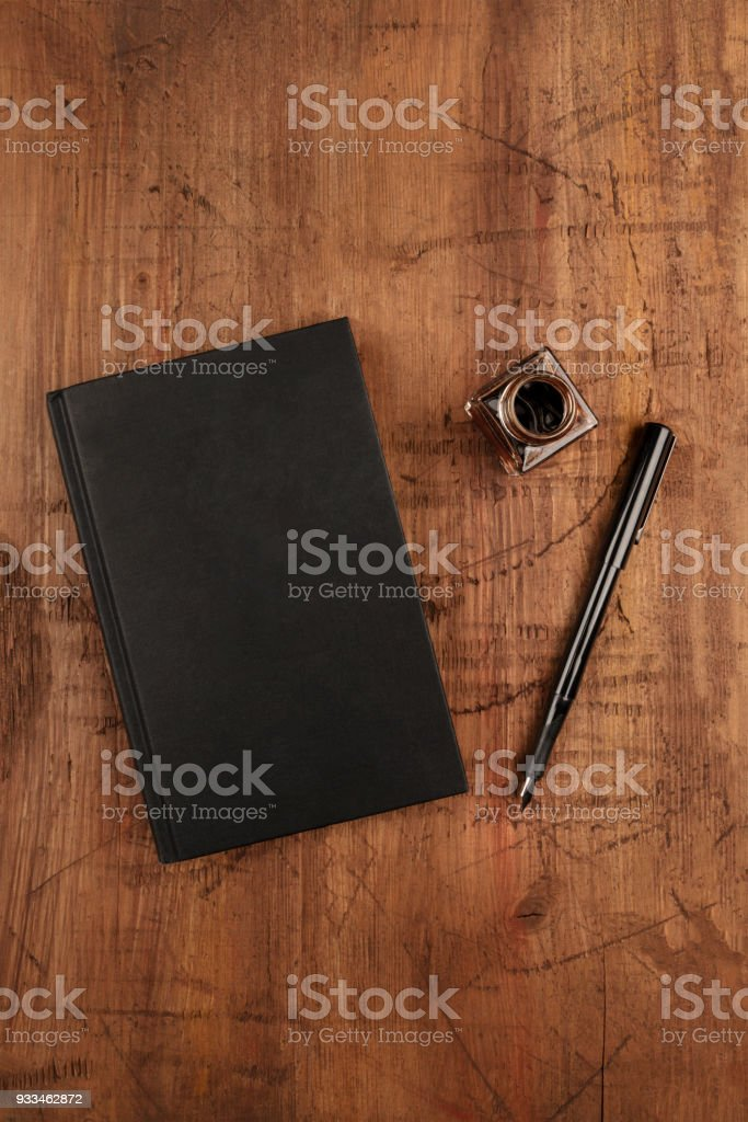 An overhead photo mockup of a black book with a fountain pen, an ink well, and a place for text stock photo