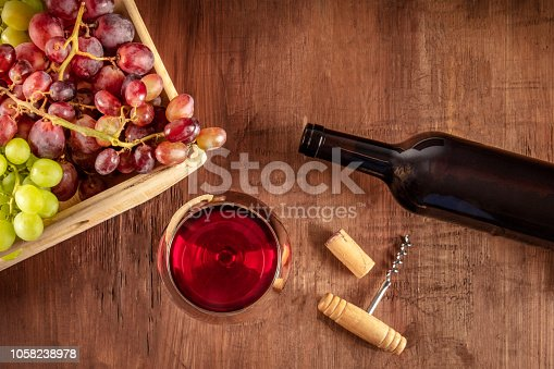 An overhead photo of a glass of red wine with a bottle, grapes, a vintage corkscew and a cork, shot from the top on a dark rustic wooden background with copy space