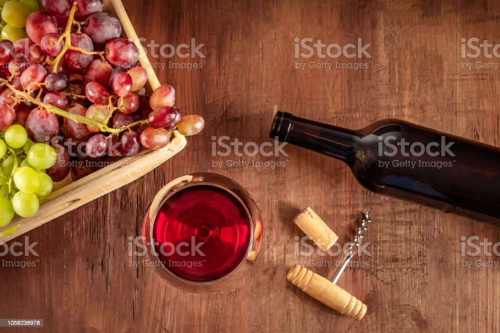 An overhead photo of a glass of red wine with a bottle, grapes, a vintage corkscew and a cork, shot from the top on a dark rustic wooden background with copy space stock photo